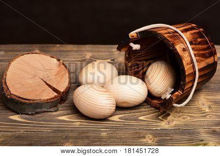 Easter Beige Wood Eggs In Wooden Bucket Near Tree Stump