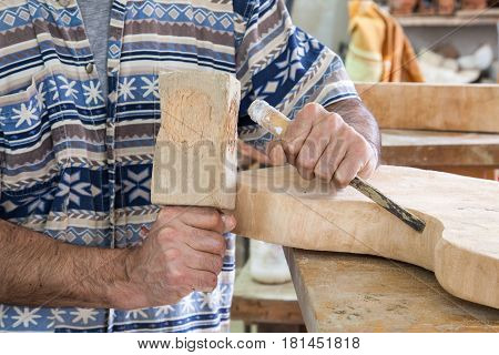 hands of artist processing wood with a chisel