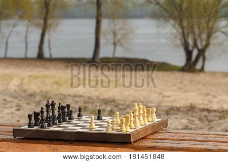 One chess pieces staying against black chess pieces Chess board with chess pieces on wooden bench with river embankment background