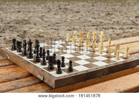 Chess board with chess pieces on wooden bench. Outdoors chess game with wooden chess pieces