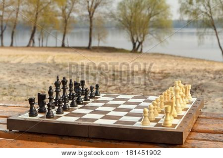 Chess board with chess pieces on wooden bench with river embankment background. Chess game with wooden chess pieces