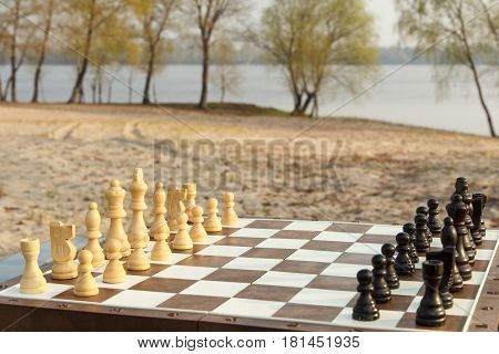 Chess board with chess pieces on river embankment. Outdoors chess game with wooden chess pieces