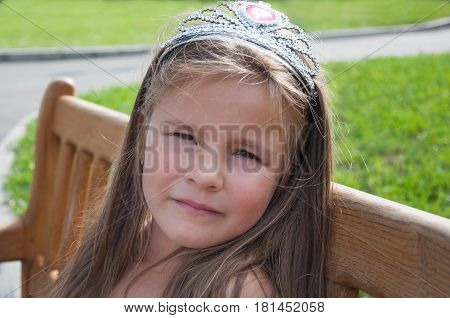 Little girl, princess, sad on a bench in the park, portrait