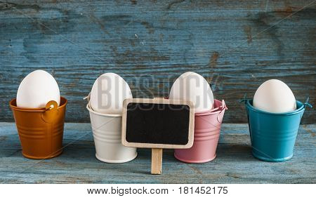 Happy Easter, white eggs in colorful buckets on the wooden background