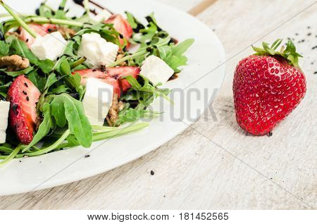Fresh salad with arugula strawberries feta cheese nuts black sesame seeds and balsamic sauce served on white plate on rustic wooden table. Healthy organic diet food concept. Selective focus.
