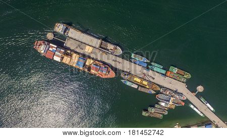 Aerial view of shipping containers waiting to be loaded on a cargo ship and vessels in Labuan port,Malaysia .