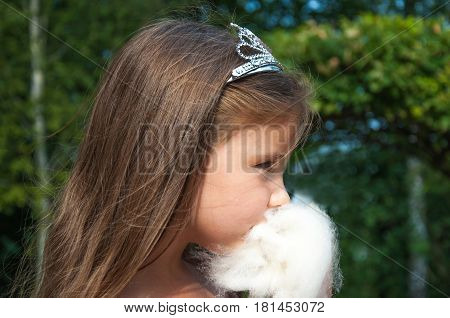 Little princess girl eating sweet cotton candy, portrait