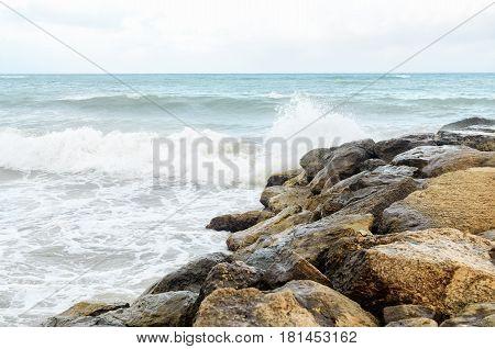 Seashore resort. Rocky coast. Surf wave on the shore.