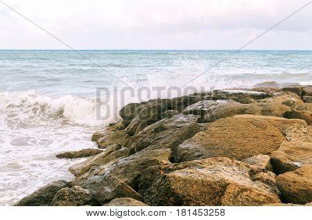 Sea shore. Rocky coast. Surf wave on the shore.
