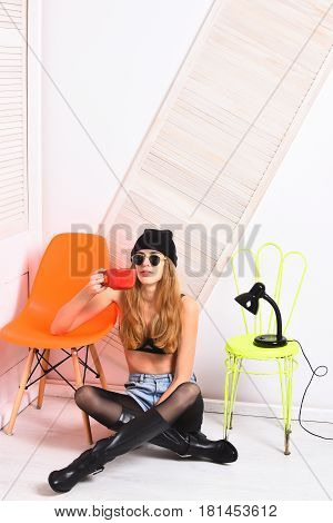 pretty woman or sexy cute girl with long blonde hair and adorable face in sunglasses bra hat sits at orange and light green chair with lamp and red tea cup on white background