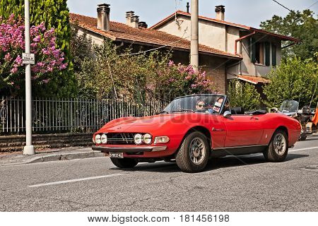 FORLI, ITALY - SEPTEMBER 11: crew on a vintage Italian sports car Fiat Dino Spider 2400 (1971) with Ferrari V6 engine in classic car rally