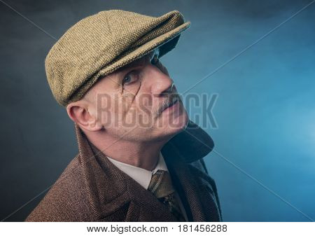 Mature man dressed as an English 1920s gangster, on a blue smoky background
