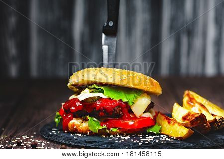 Closeup of mouth-watering, delicious homemade burgers with volatile, onions, ketchup, tomatoes, served with a knife stuck on stone board. Dark wooden background