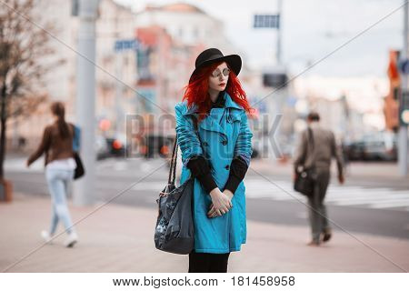 Woman with red curly hair in blue coat and black round glasses on background of big city. Red-haired girl with pale skin and bright appearance with black hat on head and bag on shoulder. Street style