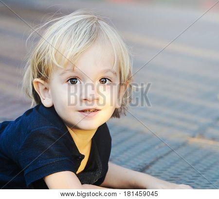 Happy Little Blond Boy Lying On The Floor