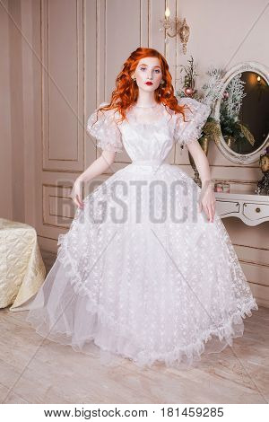 Woman with long red curly hair in a white vintage wedding dress with white pearl earrings on her ears. Red-haired girl with pale skin blue eyes a bright unusual appearance in the luxurious bedroom. Woman in dress. White wedding dress. Long nice dress