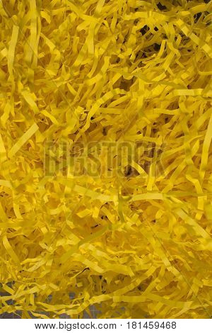This is a photograph of Yellow shredded paper fake Easter grass background