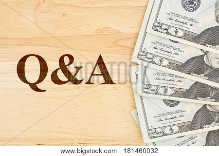 Questions and answer for your money concerns USA twenty dollar bills on a desk with text Q&A