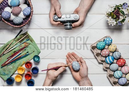 Preparation for Easter. Human hands paint Easter eggs with brushes and paints on an old white wooden background. A young man photographs the process of coloring Easter eggs on a film camera. Top view