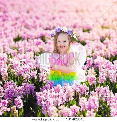 Little Girl In Fairy Costume Playing In Flower Field