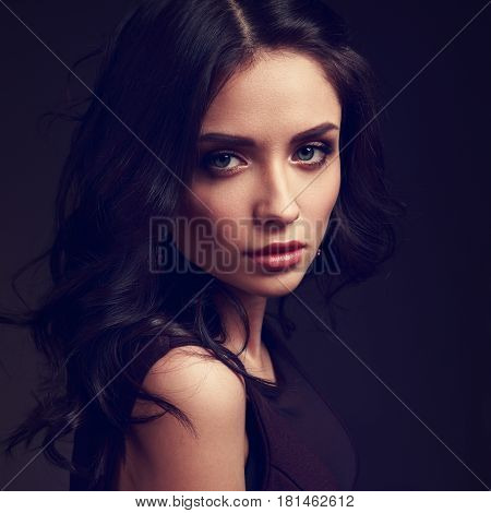 Beautiful Young Makeup Female Model With Curly Hairstyle Looking Emotional On Dark Shadow Background