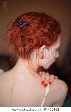 A woman with red curly hair braided in a braid in a white dress. Red-haired girl with pale skin. Pin-up girl makeup. Dutch braid closeup