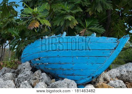 Small blue wooden wreck boat on the bed of rocks in front of tropical plants in Cayman Islands
