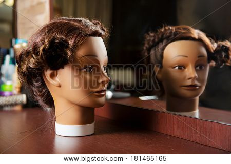 Hairdressing mannequin located on a wooden table.
