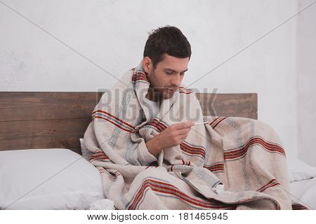 Young man sitting on bed checking the temperature feeling ill