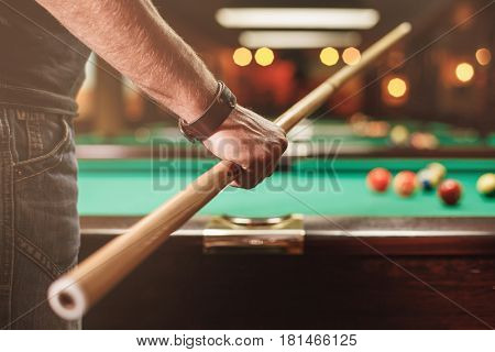 Man with cue opposite to a billiard table.