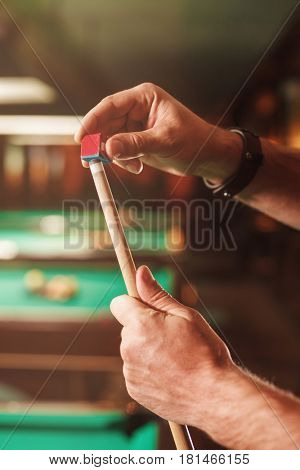 The male hands wipes a cue with chalk.