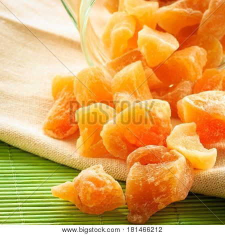 Closeup candied crystallized ginger candy pieces in glass on table. Healthy eating home remedy for nausea inflammation colds.
