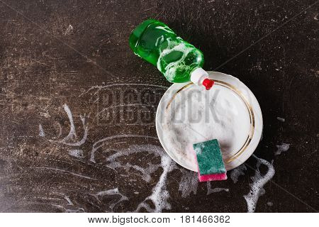 White dish detergent and sponge for dishes on a dark marble background. Hygiene. Wash the dishes