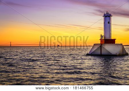 View of lighthouse and the Mackinac Bridge in Michigan at sunset