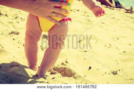 Litte baby feet standing in sand walking with human help on beach