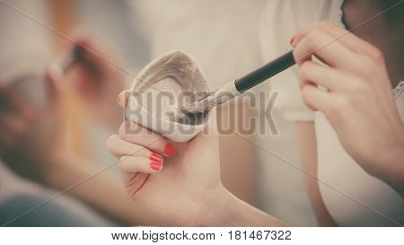 Female Hand Holding Clay Mud Mask And Brush. Skin Care.