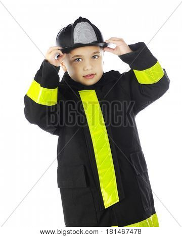 A young elementary boy putting on his chief's hat while wearing his fireman's coat.  On a white background.