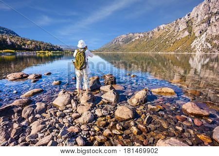 The elderly woman with green tourist backpack taking pictures of a lake in Bariloche. The concept of exotic and extreme tourism. Picturesque summer in Argentina