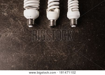 Fluorescent light bulb on a dark marble background. To save energy. Eco concept