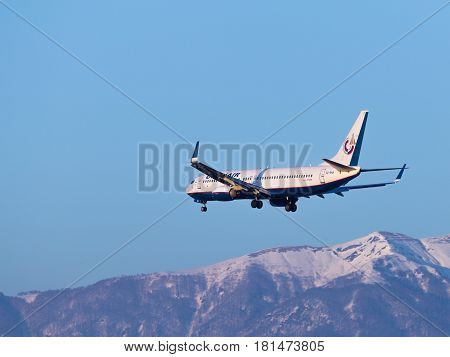 Sochi - April 3 2017: Big Boeing 737-8K5 passenger plane Orenair airlines land at Sochi airport in the evening against a clear blue sky and snowy Caucasian mountains April 3 2017 Sochi Russia