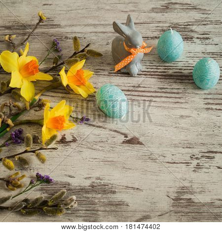 Easter holiday. Little Easter bunny on a white background. Beautiful yellow daffodils, lilac irises and pussy-willow branch. Little spring flowers on a wooden background.