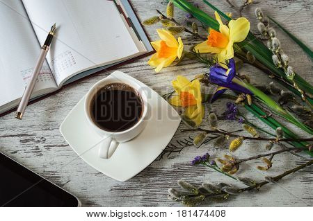 A cup of aromatic black coffee, tablet and notes. Beautiful yellow daffodils, lilac irises and pussy-willow branch. Little spring flowers on a white wooden background.