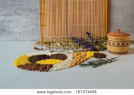 Buckwheat grain, rice, corn, pea, semolina and lentil on a white wooden background in form of horn of plenty. Wooden solt shakie.Bunches of dried wheat ears, oats and poppy seeds.