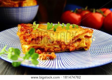 lasagna with micro greens on a blue plate