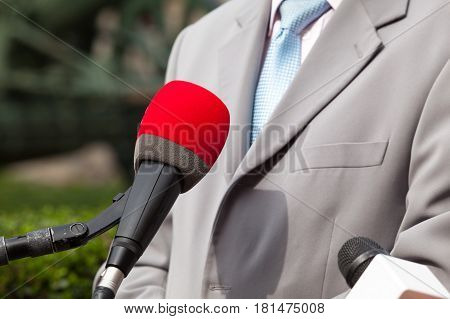 Media interview with business person or politician. News conference. Microphone.