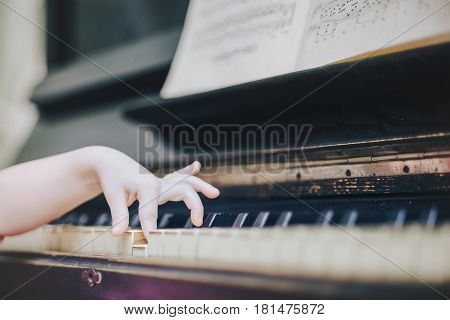 Children's fingers on the keys of a piano playing Etude