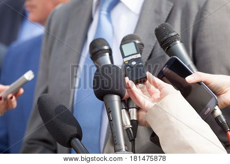 Media interview with business person. Press conference. Microphones.