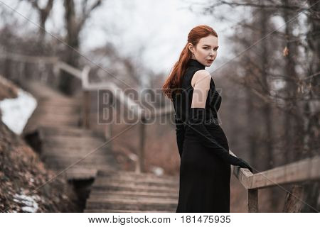 Striking girl with long red hair in black clothes. Woman in black dress and long black gloves posing on a background of winter autumn nature. Female street fashion style. Beautiful elegant model