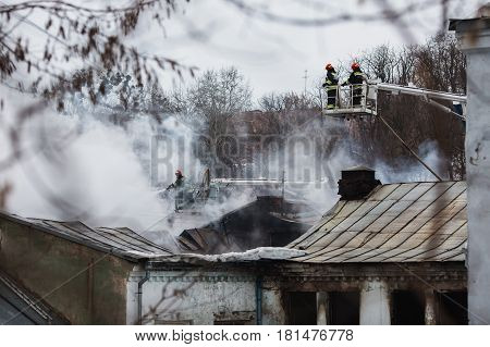 Rescuers firefighters extinguish a fire on the damage roof. The building after the fire. Burnt window. Ruined damage house. Catastrophe. Soot on the windows