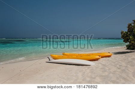 Kayak on the beach .kayaks at beautiful tropical beach with palm trees, white sand, turquoise ocean water and blue sky at Thinadhoo Islands, Maldives